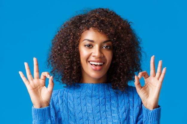Съемка крупным планом, уверенная и уверенная, уверенная в себе молодая афроамериканская женщина говорит, что все под контролем, все хорошо, все хорошо с жестом, улыбается, дает одобрение, положительный ответ, синий