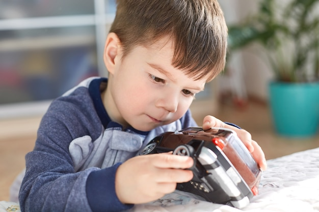 Close up shot of attractive brunet male kid plays with his favourite toy car, tries to repair wheel, has concentrated look, spends free time at home