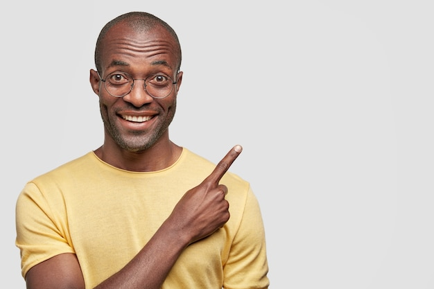 Close up shot of attractive cheerful young dark skinned african american male dressed in yellow casual t shirt