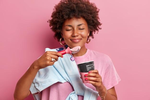 Immagine ravvicinata di attraente donna dai capelli ricci si leva in piedi con gli occhi chiusi, gode di un gusto gradevole di gelato alla fragola, indossa un maglione sopra la spalla, isolato sul muro rosa. delizioso dessert freddo