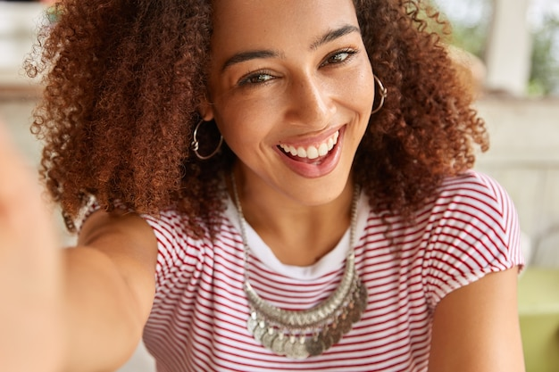 Close up shot of attractive dark skinned girl looks joyfully