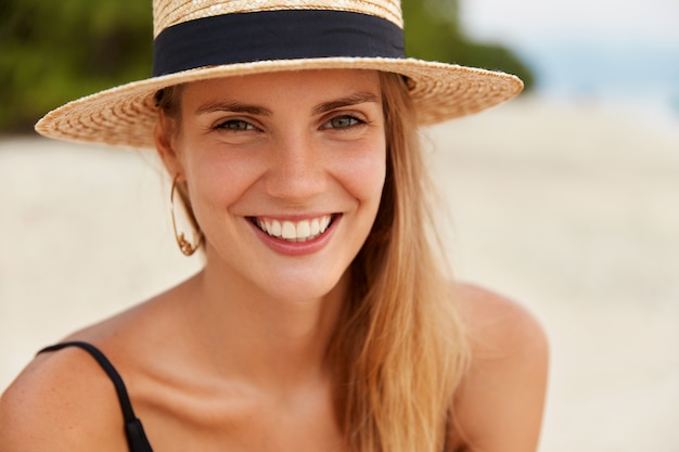 Close up shot of attractive female has warm eyes, broad smile with white even teeth, wears beach hat, recreate in luxurious resort. summer travelling and tourism concept. woman at tropical island