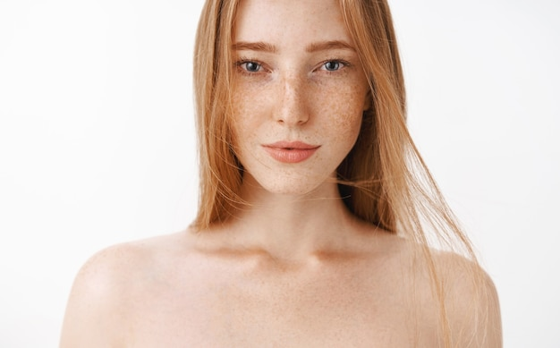 Close-up shot of attractive feminine naked redhead woman with freckles posing sensualy with sexy look in eyes standing daring having confidence in own body