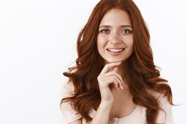 Close-up shot attractive feminine redhead woman with curly long hairstyle, freckles touch chin thoughtful, pondering curious idea, smiling intrigued and satisfied, thinking over white wall