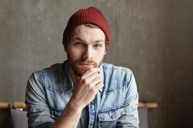 Close up shot of attractive good-looking young european bearded male dressed in fashionable denim shirt and maroon hat smiling, having thoughtful, deep and wise look, touching his beard