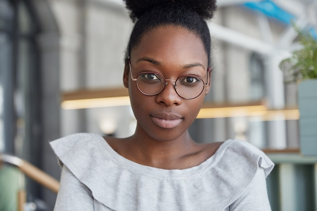 Close up shot of attractive serious female with dark skin, looks confidently directly at camera, wears round spectacles, poses in office, has break after work.