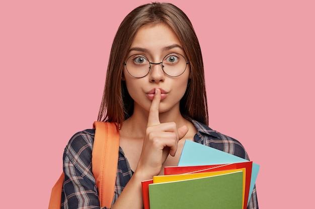 Immagine ravvicinata di attraente studente in posa contro il muro rosa con gli occhiali