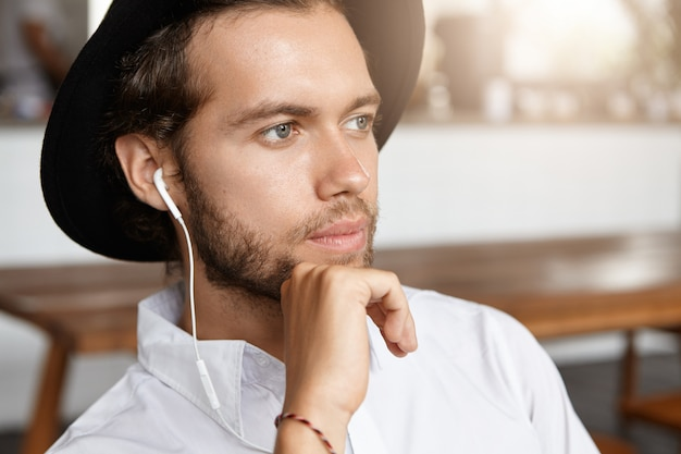 Close up shot of attractive and stylish man with beard looking pensive, listening to music online on white earphones using some electronic gadget while waiting for his girlfriend at coffee shop