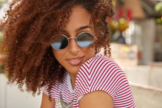 Immagine ravvicinata di donna attraente con i capelli ricci, indossa sfumature alla moda rotonde, maglietta casual, gode dell'estate, ha il proprio stile, ama i vestiti alla moda