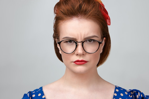 Close up shot of attractive young caucasian female teacher wearing dotted dress, red lipstick and stylish eyeglasses frowning, looking at camera with strict expression, annoyed with noisy pupils