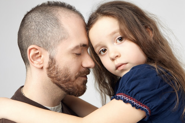 Close up shot of attractive young caucasian guy with stylish beard hugging his sad beautiful baby girl, closing eyes, expressing care and tenderness