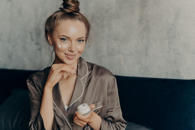 Close up shot of attractive young female model in brown silk pajama sitting on bed in morning after waking up with healthy fresh skin holding cream container in hand and applying cosmetic product