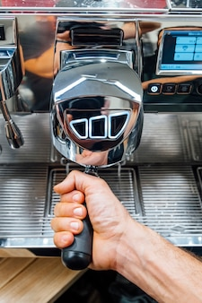 Close-up shot of barista holding filter holder while coffee machine brewing fresh espresso into glass