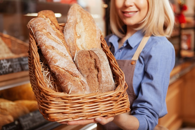 Close up shot of a basket full of delicious freshly baked bread in the hands of cheerful female baker