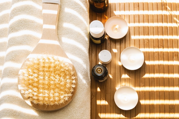 Close-up shot of bathing brush with essential oils and candles. spa concept.