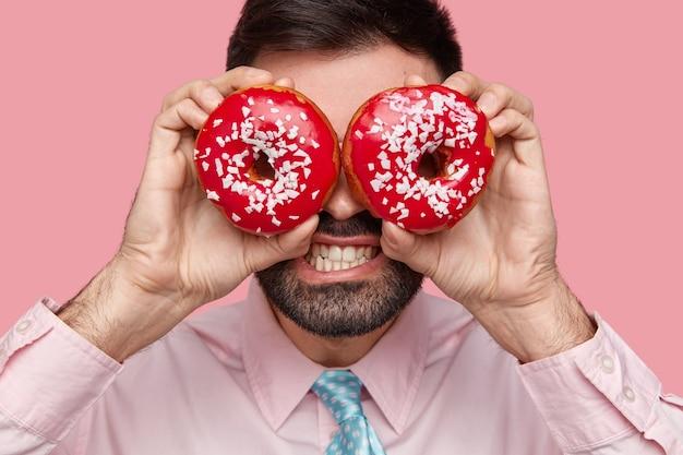 Immagine ravvicinata di barbuto uomo d'affari in camicia formale rosa chiaro copre gli occhi con due deliziose ciambelle, stringe i denti, sente la tentazione