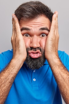 Close up shot of bearded eurpean man squeezes cheeks makes funny carefree face
