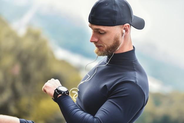 ワークアウトセッション後のクローズアップショットひげを生やしたスポーツマンは、フィットネスの結果を確認します。スポーツトラッカーリストバンドを身に着けている大人の男。