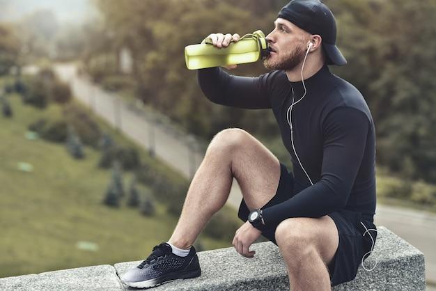 근접 촬영 수염 난 낚시를 좋아하는 남자는 휴식을 취하고 운동 세션 후 물을 마신다.