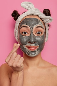 Close up shot of beautiful asian woman applies purifying black mask on face, has beauty treatments, makes korean like sign, wears grey headband, stands shirtless against pink wall in bathroom
