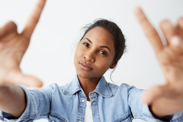 Primo piano del bellissimo modello affascinante afroamericano con pelle scura sana con un debole sorriso, in posa al chiuso contro il muro bianco, indossa una camicia di jeans.