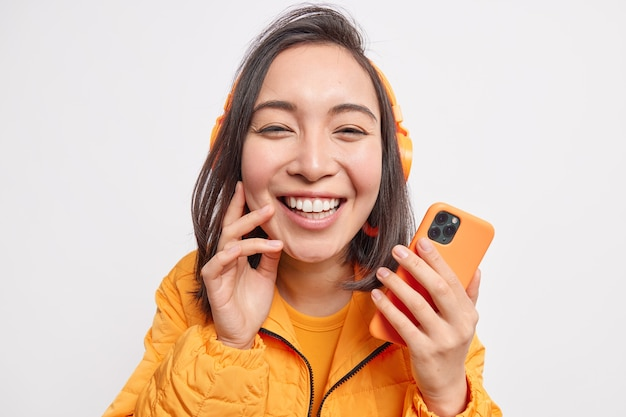 Close up shot of beautiful cheerful asian woman smiles broadly from delight enjoys listening favorite music holds mobile phone dressed in orange jacket isolated over white  wall.