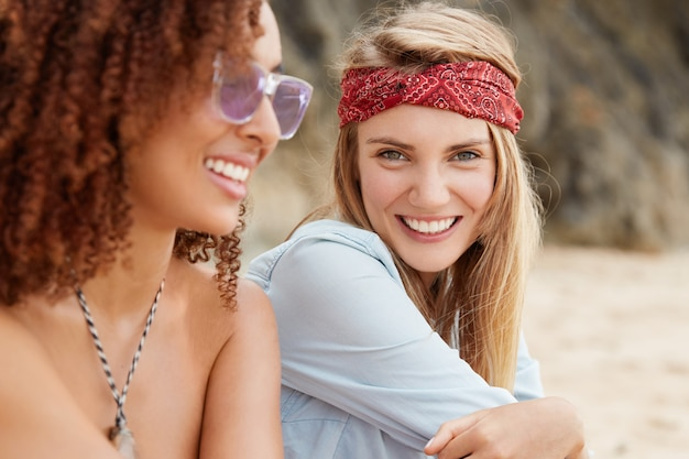 Close up shot of beautiful cheerful young blonde woman wears red headband and shirt, has pleasant talk with dark skinned afro american female friend, spend spare time outdoor near ocean view
