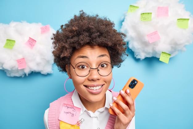 Immagine ravvicinata di bella donna curiosa lavoratore di ufficio sorride felicemente detiene il cellulare controlla newsfeed circondato da adesivi colorati con informazioni scritte o elenco da fare