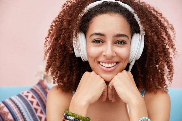 Immagine ravvicinata di bella giovane donna africana felice ha un ampio sorriso, gode della melodia preferita in cuffia