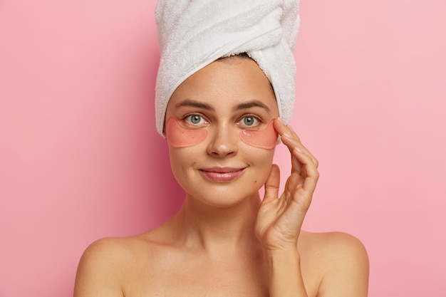 Close up shot of beautiful european female model makes spa procedures after taking shower, applies collagen patches under eyes, has anti aging treatment, stands indoor