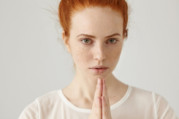 Close up shot of beautiful european girl with ginger hair and freckles holding hands in namaste in front of her while meditating alone early in the morning. people, yoga and meditation concept