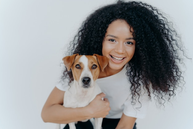 Close up shot of beautiful happy afro woman with bushy curly hair, embraces favourite dog and have fun together