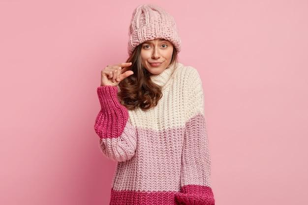 Immagine ravvicinata di bella signora forma qualcosa di minuscolo, fa un gesto della mano, ha dispiaciuto l'espressione del viso, indossa abiti invernali alla moda, posa contro il muro rosa molto piccolo o piccolo
