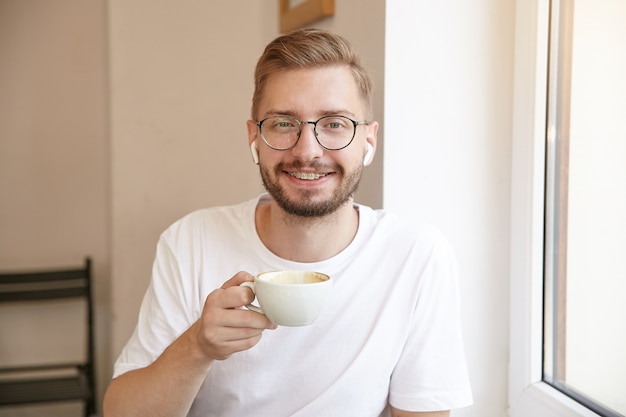 Colpo del primo piano del bel maschio con la tazza in mano, con gli occhiali e le cuffie, sorridente sinceramente, in posa sopra l'interno della casa