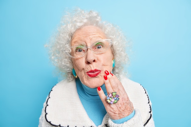Close up shot of beautiful wrinkled curly mature woman examines her skin touches face has red manicure and lips wears jewelry stylish clothes