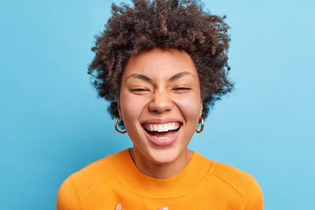 Close up shot of beautiful young african american woman with natural curly hair smiles broadly has positive look  being in good mood wears orange jumper isolated over blue wall