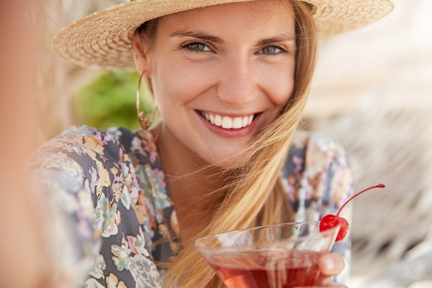 Close up shot of beautiful young female has summer party with friends, enjoys drinking tasty fruit beverage, makes selfie with cheerful smile, dressed in fashionable clothing