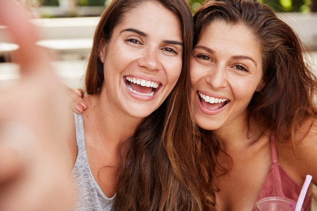 Close up shot of beutiful females with glad looks pose at camera with cheerful expression, pose for selfie