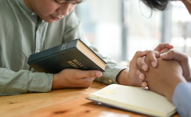 Close up shot of the bible and people praying