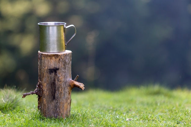 Close-up shot, big shiny tin mug on isolated tree stump outdoors on grassy sunny summer forest