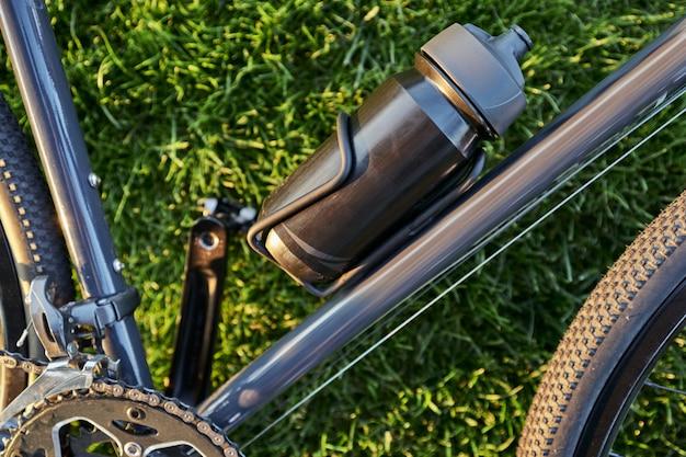 Close up shot of black aluminum water bottle on black road bike lying on the