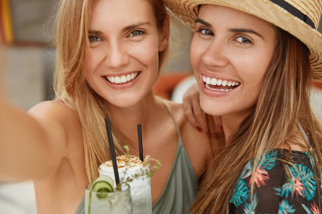 Close up shot of blonde and brunette women have broad smiles, pose at camera and make selfie, hold exotic cocktails, have summer vacations. people, happiness, recreation and lifestyle concept