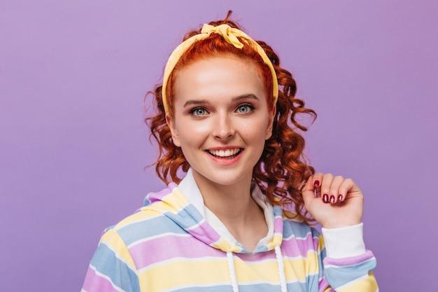 Colpo del primo piano della ragazza dagli occhi azzurri con la medicazione gialla dei capelli che posa sulla parete lilla