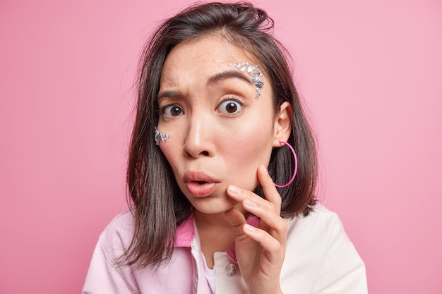 Close up shot of brunette young asian woman keeps hand on face looks with great wonder  raises eyebrows reacts on shocking news cannot believe her eyes isolated over pink wall