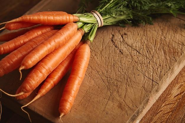 Immagine ravvicinata di un mucchio di carote fresche mature su un vecchio tagliere con tagli profondi