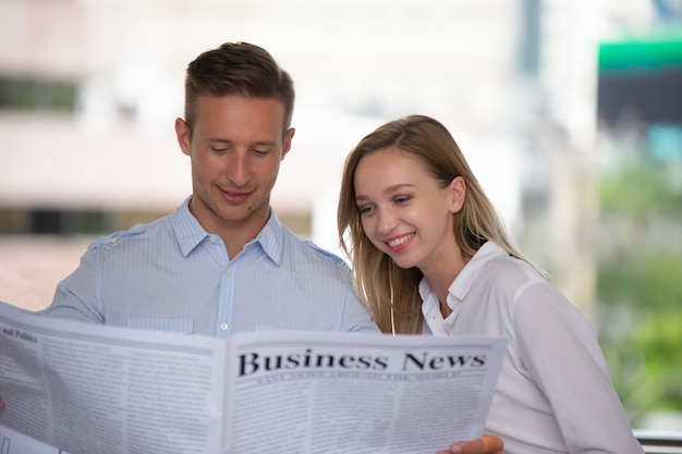 Close-up shot of a businessman in black suite reading the latest news