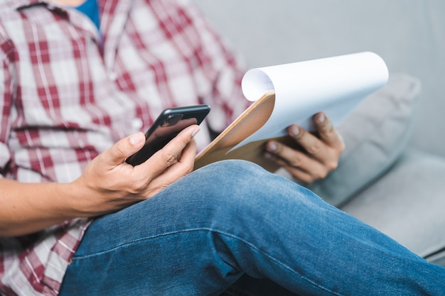 Close-up shot of a businessman in casual wear looking at the business report on document and smartphone while sitting on the couch in relaxed posture in the home office. business stock photo
