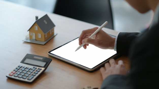 Close-up shot of businesspeople use a pen to write on a tablet with model house and a calculator on the table.