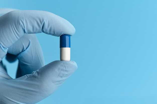 Close-up shot of capsule pill in nurse's hand on blue background. female hand in a medical glove is holding an antiviral capsule.