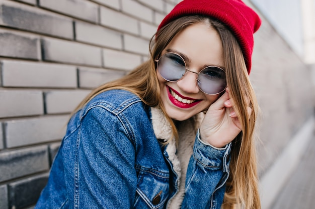 Close-up shot of caucasian fascinating girl in casual red dress. photo of enthusiastic white woman wears denim clothes in spring day.